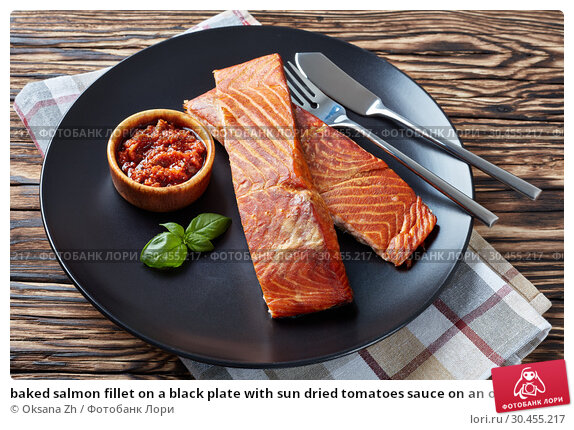 baked salmon fillet on a black plate with sun dried tomatoes sauce on an old wooden table. Стоковое фото, фотограф Oksana Zh / Фотобанк Лори
