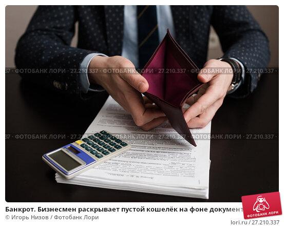 Купить «Банкрот. Бизнесмен раскрывает пустой кошелёк на фоне документов и калькулятора», эксклюзивное фото № 27210337, снято 6 ноября 2017 г. (c) Игорь Низов / Фотобанк Лори