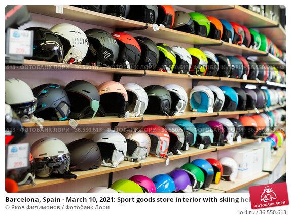 Barcelona, Spain - March 10, 2021: Sport goods store interior with skiing helmets on shelves. Редакционное фото, фотограф Яков Филимонов / Фотобанк Лори