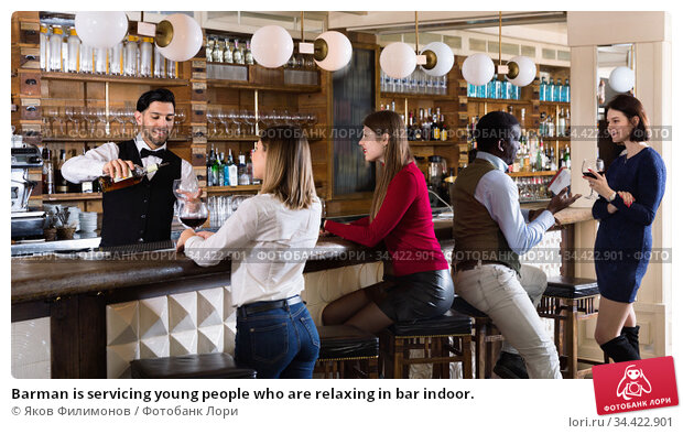 Barman is servicing young people who are relaxing in bar indoor. Стоковое фото, фотограф Яков Филимонов / Фотобанк Лори