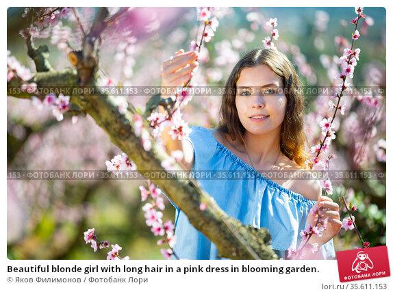 Beautiful blonde girl with long hair in a pink dress in blooming garden. Стоковое фото, фотограф Яков Филимонов / Фотобанк Лори