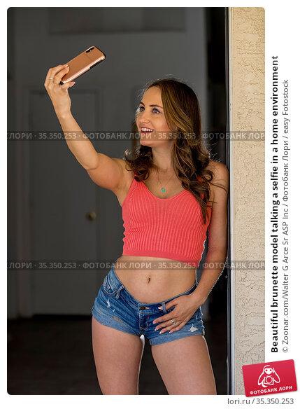 Beautiful brunette model talking a selfie in a home environment. Стоковое фото, фотограф Zoonar.com/Walter G Arce Sr ASP Inc / easy Fotostock / Фотобанк Лори