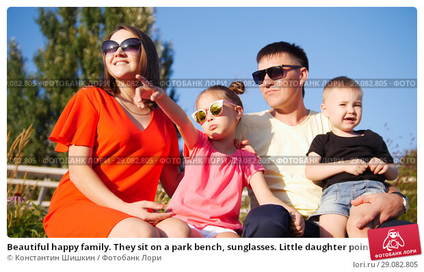 Купить «Beautiful happy family. They sit on a park bench, sunglasses. Little daughter pointing her finger at the sky», фото № 29082805, снято 21 сентября 2018 г. (c) Константин Шишкин / Фотобанк Лори