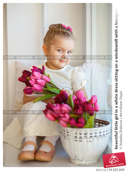 beautiful little girl in a white dress sitting on a windowsill with a bouquet of pink tulips. Стоковое фото, фотограф Nataliia Zhekova / Фотобанк Лори