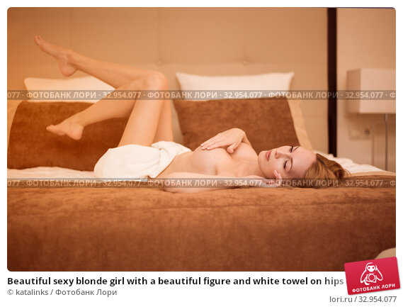 Beautiful sexy blonde girl with a beautiful figure and white towel on hips cover her breast in bed. Стоковое фото, фотограф katalinks / Фотобанк Лори