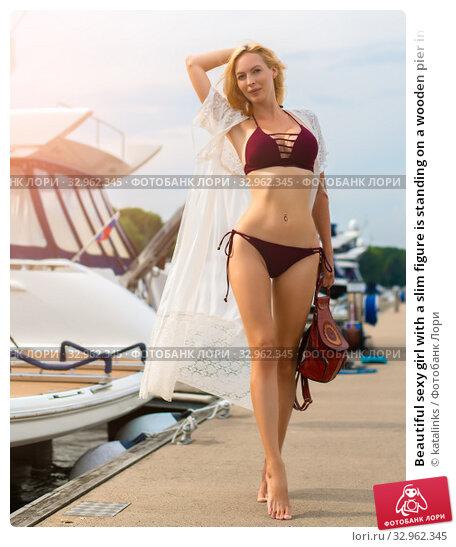 Купить «Beautiful sexy girl with a slim figure is standing on a wooden pier in a yacht club», фото № 32962345, снято 27 июня 2017 г. (c) katalinks / Фотобанк Лори