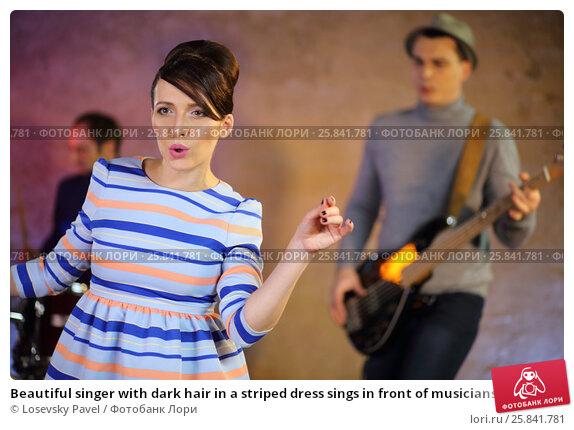 Купить «Beautiful singer with dark hair in a striped dress sings in front of musicians», фото № 25841781, снято 9 декабря 2014 г. (c) Losevsky Pavel / Фотобанк Лори