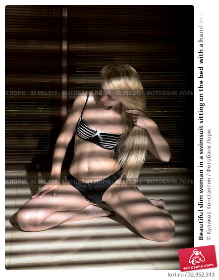 Beautiful slim woman in a swimsuit sitting on the bed  with a hand in long hair in the light from the window through the blinds. Стоковое фото, фотограф Куликов Константин / Фотобанк Лори