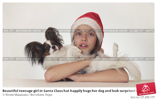 Купить «Beautiful teenage girl in Santa Claus hat happily hugs her dog and look surprised on white background», фото № 27205177, снято 11 декабря 2018 г. (c) Юлия Машкова / Фотобанк Лори