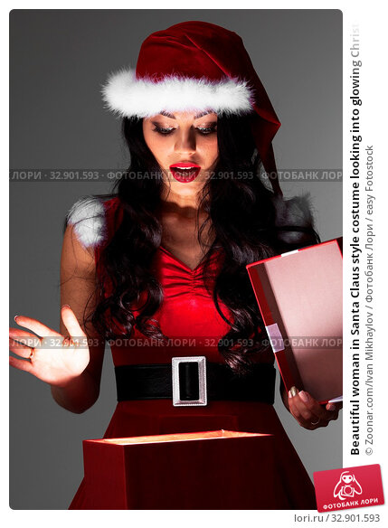 Beautiful woman in Santa Claus style costume looking into glowing Christmas gift box. Стоковое фото, фотограф Zoonar.com/Ivan Mikhaylov / easy Fotostock / Фотобанк Лори