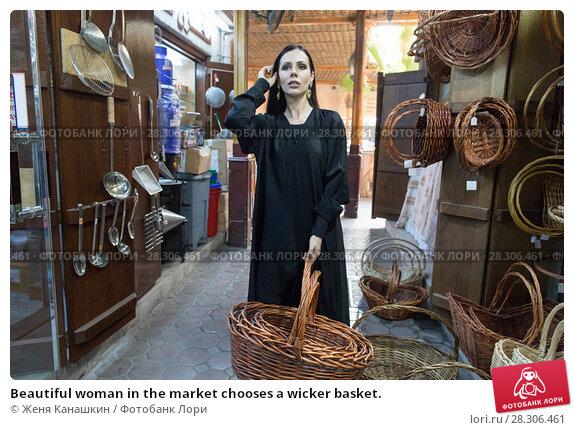 Купить «Beautiful woman in the market chooses a wicker basket.», фото № 28306461, снято 13 марта 2018 г. (c) Женя Канашкин / Фотобанк Лори