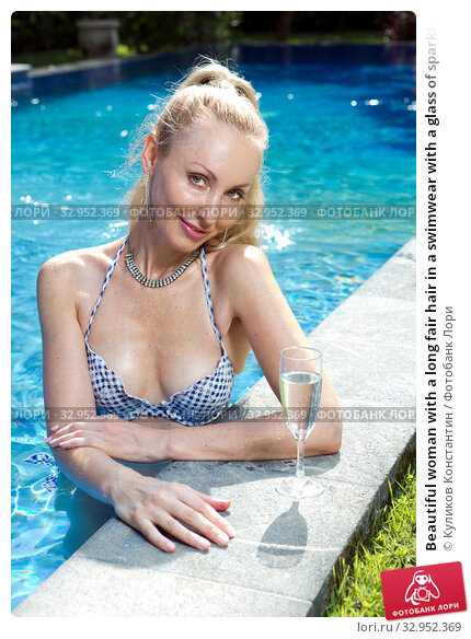 Beautiful woman with a long fair hair in a swimwear with a glass of sparkling wine in the pool with bright blue water. Стоковое фото, фотограф Куликов Константин / Фотобанк Лори