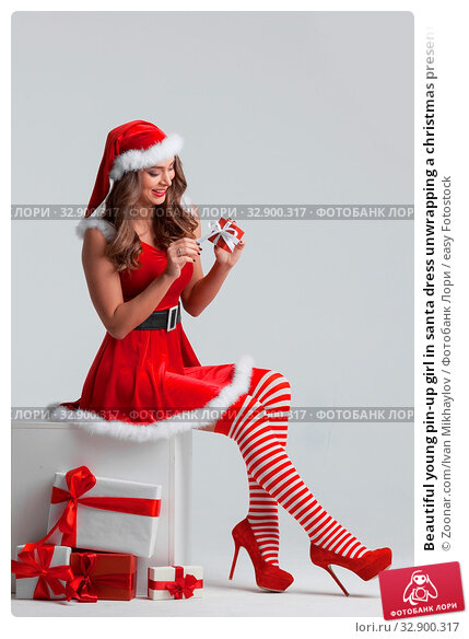 Beautiful young pin-up girl in santa dress unwrapping a christmas present. Стоковое фото, фотограф Zoonar.com/Ivan Mikhaylov / easy Fotostock / Фотобанк Лори