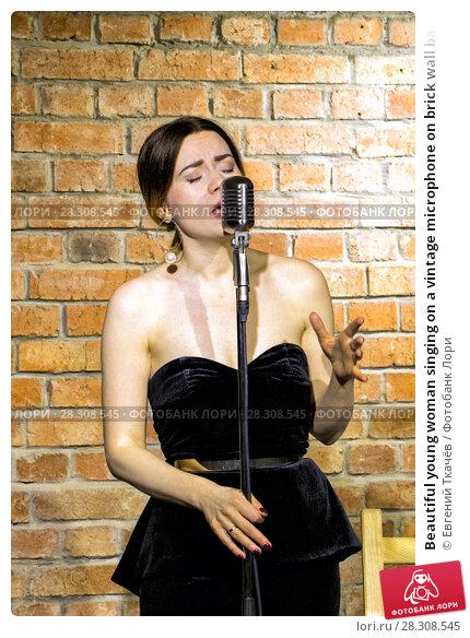 Купить «Beautiful young woman singing on a vintage microphone on brick wall background», фото № 28308545, снято 2 декабря 2017 г. (c) Евгений Ткачёв / Фотобанк Лори