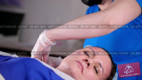 Купить «Beauty clinic. Young woman gets professional facial massage by masseur in mask.», видеоролик № 29491081, снято 19 февраля 2019 г. (c) Константин Шишкин / Фотобанк Лори