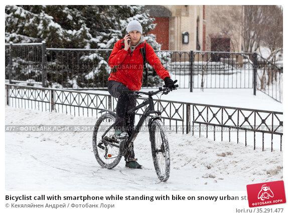 Bicyclist call with smartphone while standing with bike on snowy urban street, riding on bicycle at winter season. Стоковое фото, фотограф Кекяляйнен Андрей / Фотобанк Лори