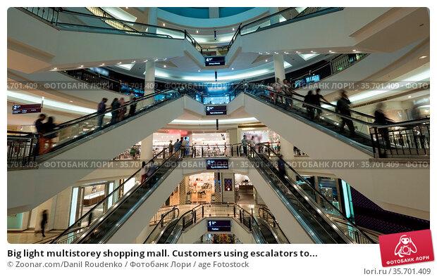 Big light multistorey shopping mall. Customers using escalators to... Стоковое фото, фотограф Zoonar.com/Danil Roudenko / age Fotostock / Фотобанк Лори