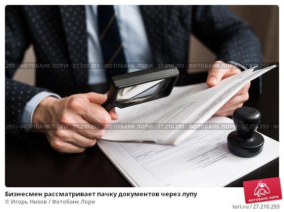 Бизнесмен рассматривает пачку документов через лупу. Стоковое фото, фотограф Игорь Низов / Фотобанк Лори