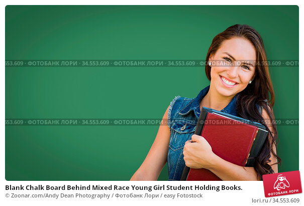 Blank Chalk Board Behind Mixed Race Young Girl Student Holding Books. Стоковое фото, фотограф Zoonar.com/Andy Dean Photography / easy Fotostock / Фотобанк Лори