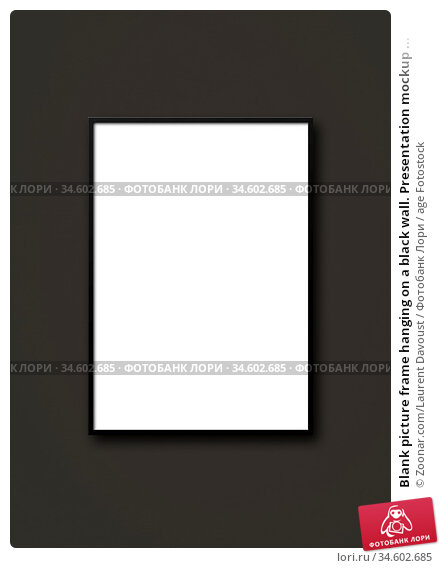Blank picture frame hanging on a black wall. Presentation mockup ... Стоковое фото, фотограф Zoonar.com/Laurent Davoust / age Fotostock / Фотобанк Лори
