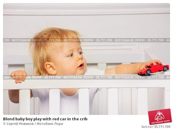 Blond baby boy play with red car in the crib. Стоковое фото, фотограф Сергей Новиков / Фотобанк Лори