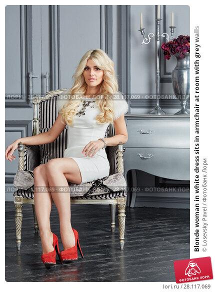 Купить «Blonde woman in white dress sits in armchair at room with grey walls», фото № 28117069, снято 14 ноября 2015 г. (c) Losevsky Pavel / Фотобанк Лори