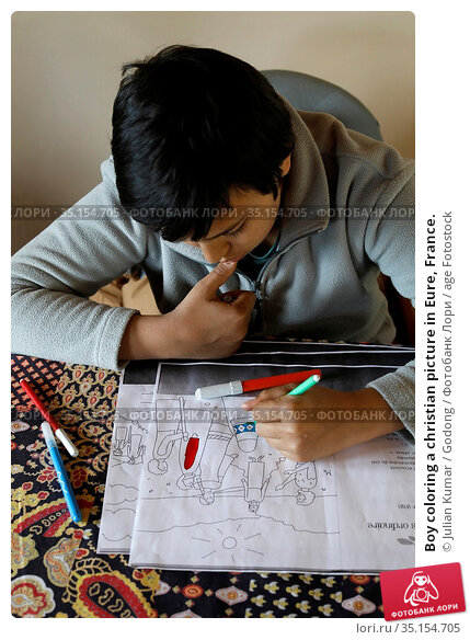 Boy coloring a christian picture in Eure, France. Стоковое фото, фотограф Julian Kumar / Godong / age Fotostock / Фотобанк Лори