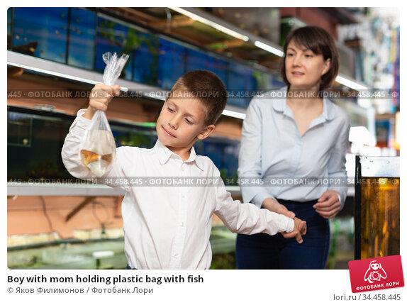 Boy with mom holding plastic bag with fish. Стоковое фото, фотограф Яков Филимонов / Фотобанк Лори