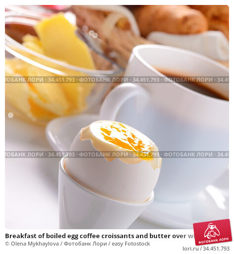 Breakfast of boiled egg coffee croissants and butter over white background... Стоковое фото, фотограф Olena Mykhaylova / easy Fotostock / Фотобанк Лори
