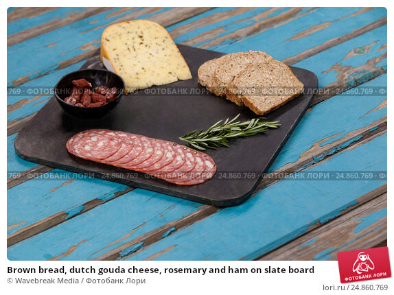 Купить «Brown bread, dutch gouda cheese, rosemary and ham on slate board», фото № 24860769, снято 16 сентября 2016 г. (c) Wavebreak Media / Фотобанк Лори