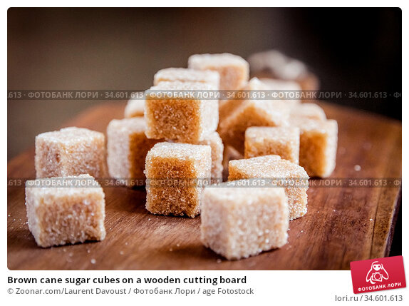 Brown cane sugar cubes on a wooden cutting board. Стоковое фото, фотограф Zoonar.com/Laurent Davoust / age Fotostock / Фотобанк Лори