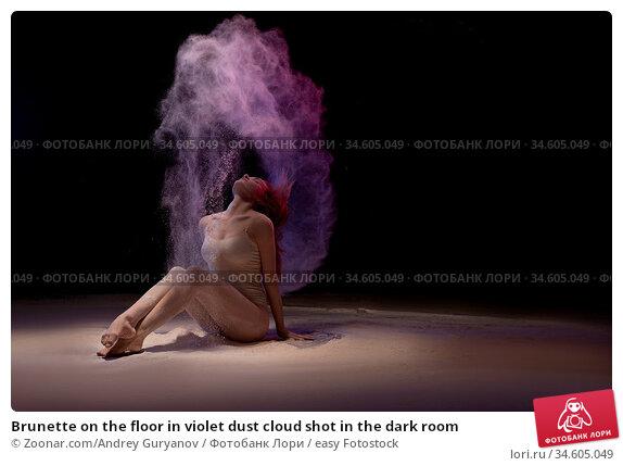 Brunette on the floor in violet dust cloud shot in the dark room. Стоковое фото, фотограф Zoonar.com/Andrey Guryanov / easy Fotostock / Фотобанк Лори