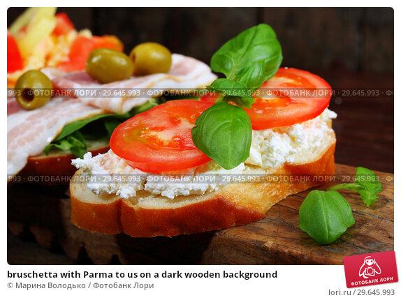 bruschetta with Parma to us on a dark wooden background. Стоковое фото, фотограф Марина Володько / Фотобанк Лори