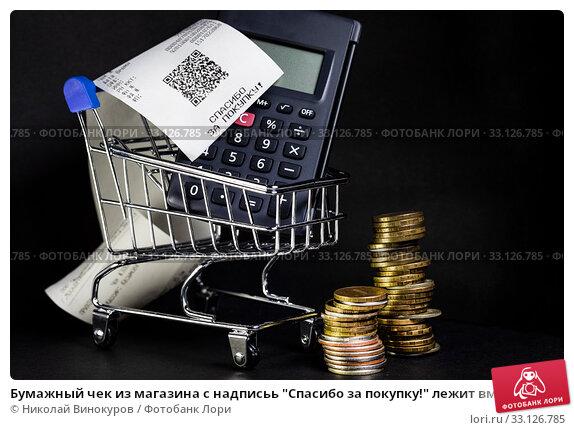 """Купить «Бумажный чек из магазина с надписьь """"Спасибо за покупку!"""" лежит вместе с калькулятором в магазинной тележке на черном фоне», фото № 33126785, снято 15 февраля 2020 г. (c) Николай Винокуров / Фотобанк Лори"""