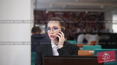 Business concept. A woman sit by the table and talking on her phone. Стоковое видео, видеограф Константин Шишкин / Фотобанк Лори