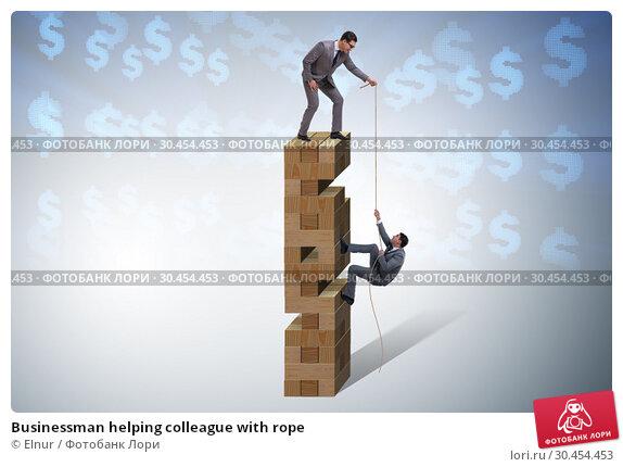 Businessman helping colleague with rope. Стоковое фото, фотограф Elnur / Фотобанк Лори