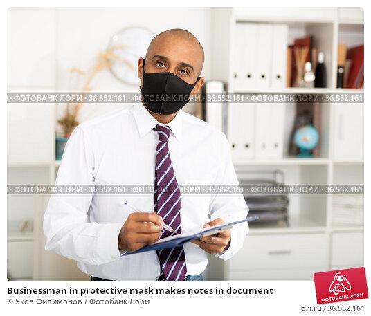 Businessman in protective mask makes notes in document. Стоковое фото, фотограф Яков Филимонов / Фотобанк Лори
