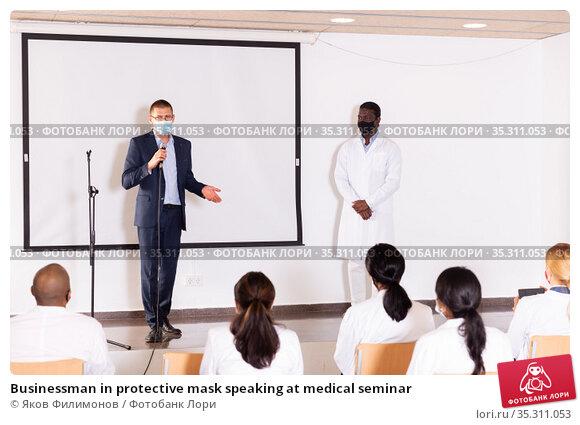 Businessman in protective mask speaking at medical seminar. Стоковое фото, фотограф Яков Филимонов / Фотобанк Лори