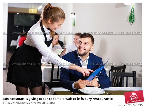 Купить «Businessman is giving order to female waiter in luxury restaurante», фото № 28163245, снято 18 декабря 2017 г. (c) Яков Филимонов / Фотобанк Лори