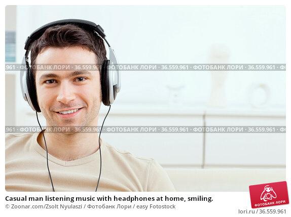 Casual man listening music with headphones at home, smiling. Стоковое фото, фотограф Zoonar.com/Zsolt Nyulaszi / easy Fotostock / Фотобанк Лори