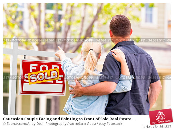 Caucasian Couple Facing and Pointing to Front of Sold Real Estate... Стоковое фото, фотограф Zoonar.com/Andy Dean Photography / easy Fotostock / Фотобанк Лори