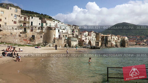 Купить «CEFALU, ITALY - APRIL 14, 2019: The coastal line of the central part of the Sicilian town of Cefalu on a sunny spring day. Cefalu is one of the major tourist attractions in the Sicily region, Italy», видеоролик № 30855821, снято 14 апреля 2019 г. (c) Алексей Кузнецов / Фотобанк Лори