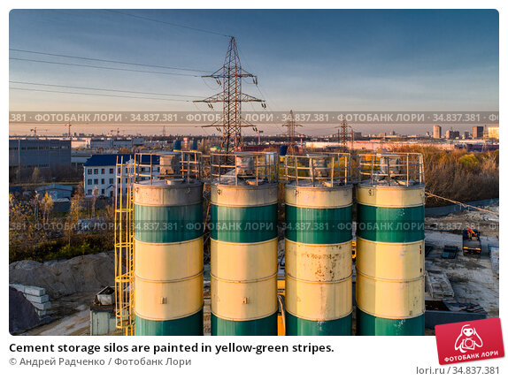 Cement storage silos are painted in yellow-green stripes. Стоковое фото, фотограф Андрей Радченко / Фотобанк Лори