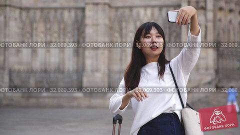 Купить «Charming chinese female tourist making selfie on the background of landmark», видеоролик № 32069393, снято 17 октября 2019 г. (c) Яков Филимонов / Фотобанк Лори