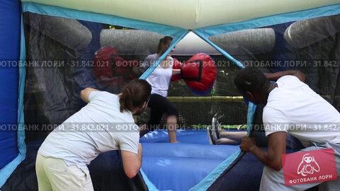 Cheerful adult women in big boxing gloves having fun on inflatable ring in outdoor amusement park. Стоковое видео, видеограф Яков Филимонов / Фотобанк Лори