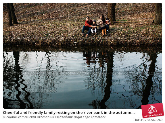 Cheerful and friendly family resting on the river bank in the autumn... Стоковое фото, фотограф Zoonar.com/Oleksii Hrecheniuk / age Fotostock / Фотобанк Лори