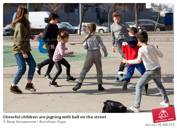 Cheerful children are jogning with ball on the street. Стоковое фото, фотограф Яков Филимонов / Фотобанк Лори