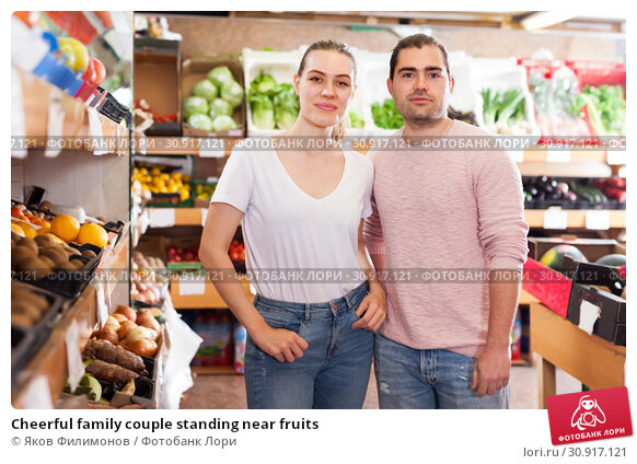 Купить «Cheerful family couple standing near fruits», фото № 30917121, снято 27 апреля 2019 г. (c) Яков Филимонов / Фотобанк Лори