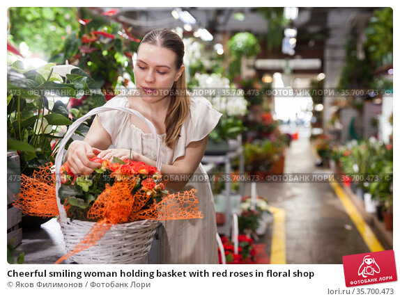 Cheerful smiling woman holding basket with red roses in floral shop. Стоковое фото, фотограф Яков Филимонов / Фотобанк Лори