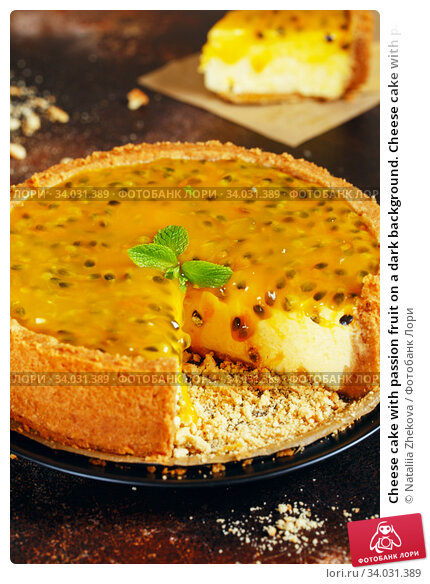 Cheese cake with passion fruit on a dark background. Cheese cake with passion fruit sauce on top, decorated with mint leaves. Стоковое фото, фотограф Nataliia Zhekova / Фотобанк Лори